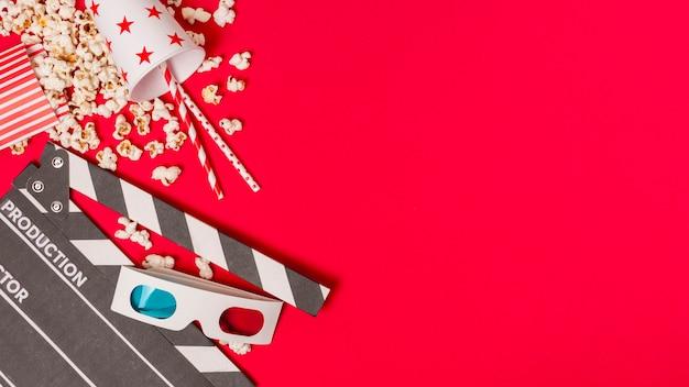 Claquete; pipocas e takeaway vidro com canudos e pipocas em fundo vermelho Foto Premium