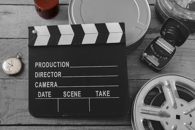 Claquete preto e branco, rolos de filme, relógio de bolso e medidor de exposição filmados de cima em uma placa de madeira Foto Premium