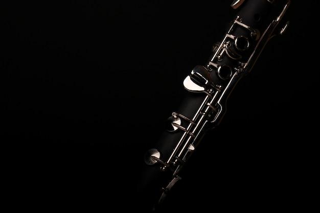 Clarinete de instrumento musical em fundo preto Foto Premium