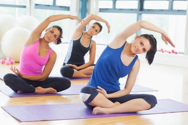 Classe e instrutor fazendo alongamentos de pilates Foto Premium