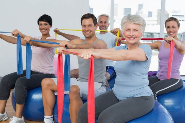 Classe segurando cintos de exercício enquanto está sentado em bolas de fitness Foto Premium