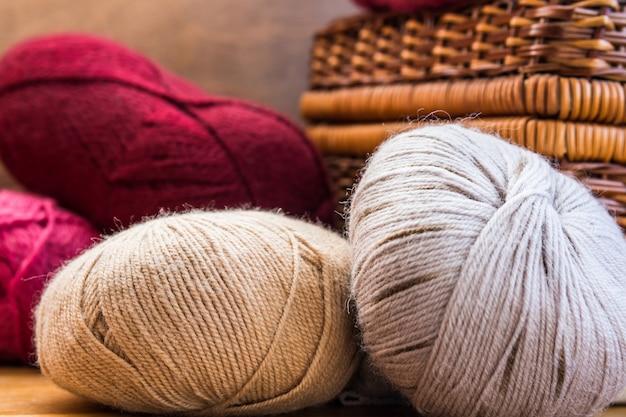 Clews bolas de fios de lã cinza bege vermelho natural, cesta de artesanato de vime Foto Premium