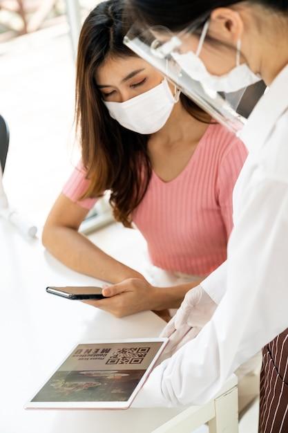 Cliente asiático escanear o menu online do código qr da garçonete com máscara e protetor facial. o cliente sentou-se na mesa de distanciamento social para um novo estilo de vida normal em um restaurante após a pandemia de coronavírus covid-19 Foto Premium
