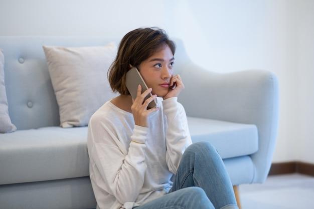 Cliente asiático pensativo sério que alcança o apoio pelo telefone Foto gratuita