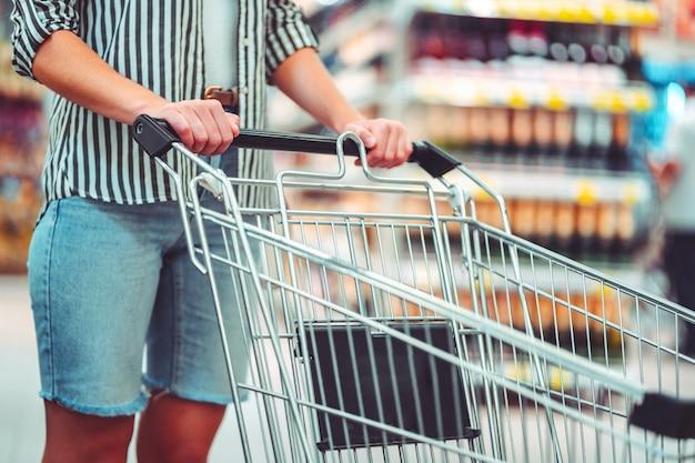 Cliente com carrinho de compras no corredor do supermercado. comprando comida no supermercado Foto Premium