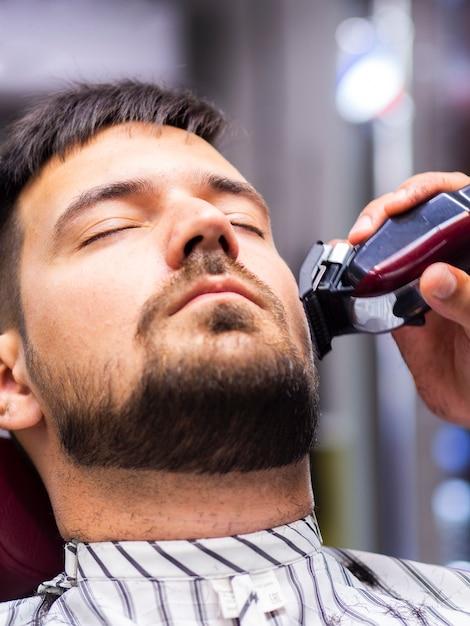 Cliente com os olhos fechados recebendo um corte Foto gratuita