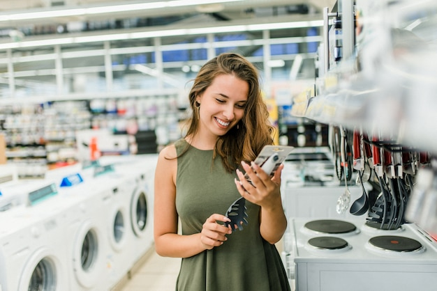 Cliente da fêmea adulta que escolhe acessórios novos da cozinha. Foto Premium