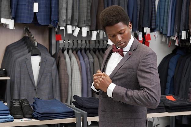 Cliente de boutiwue vestindo terno, olhando para o casaco. Foto gratuita