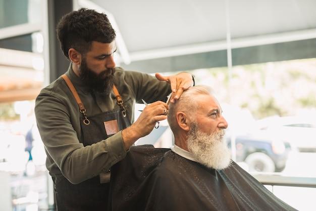 Cliente de corte de barbeiro na barbearia Foto gratuita