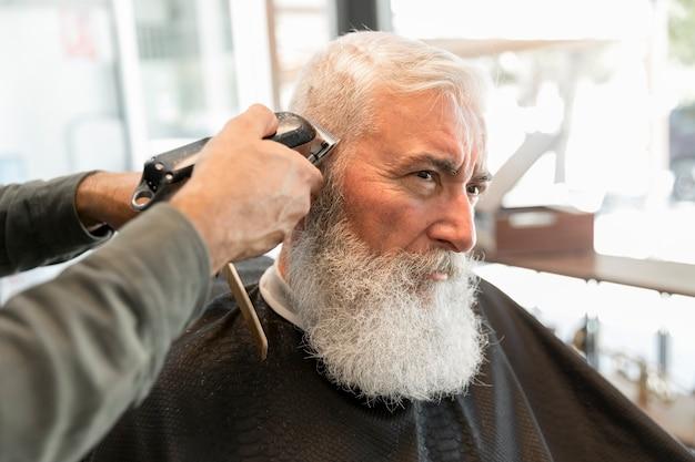 Cliente do aparamento do barbeiro no salão de beleza Foto gratuita