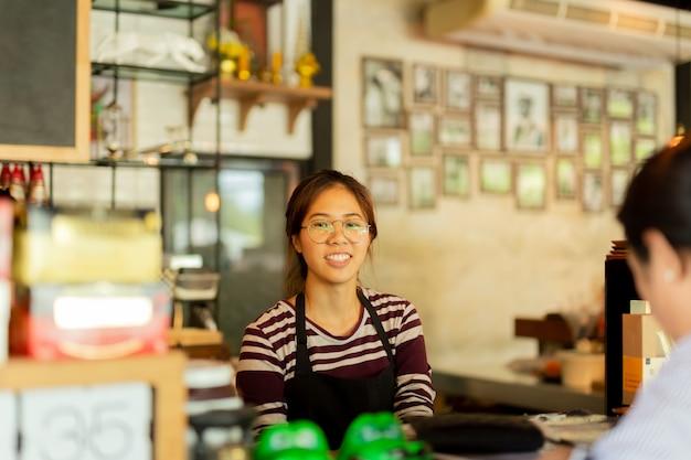Cliente do serviço do barista da jovem mulher com a cara do sorriso na barra contrária no café. Foto Premium
