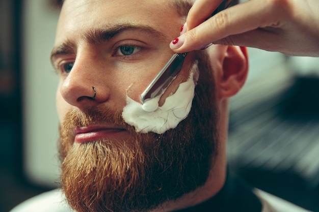 Cliente durante o barbear na barbearia. barbeiro feminino no salão. igualdade de gênero. mulher na profissão masculina. mãos fechadas Foto gratuita