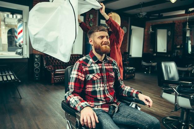 Cliente durante o barbear na barbearia. barbeiro feminino no salão. igualdade de gênero. mulher na profissão masculina. Foto gratuita