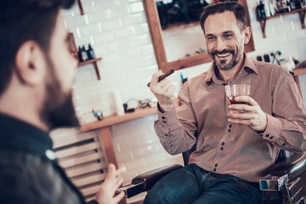 Cliente está bebendo uísque em uma barbearia Foto Premium
