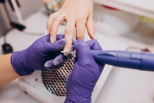 Cliente fazendo manicure em um salão de beleza Foto gratuita