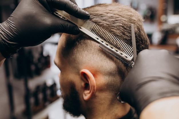 Cliente fazendo o corte de cabelo em um salão de barbearia Foto gratuita