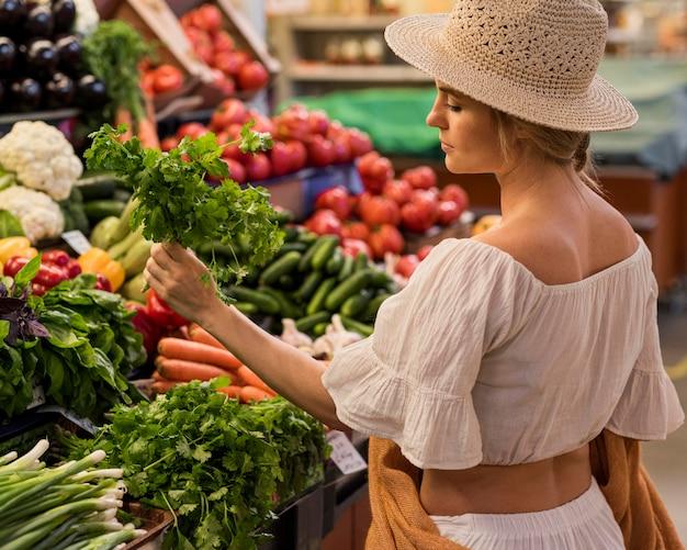 Cliente feliz comprando folhas de salsa Foto gratuita