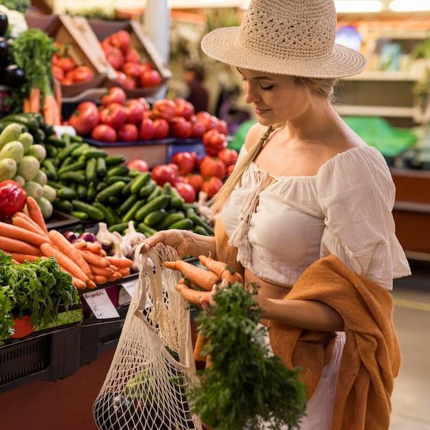 Cliente feliz comprando vegetais Foto gratuita