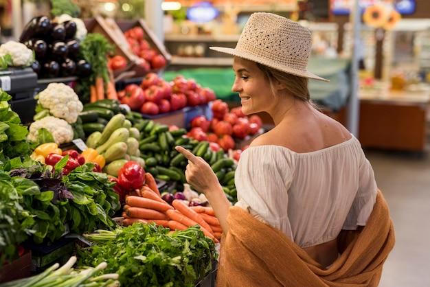 Cliente feliz olhando vegetais Foto gratuita