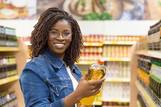 Cliente jovem sorridente, segurando a garrafa de óleo Foto gratuita