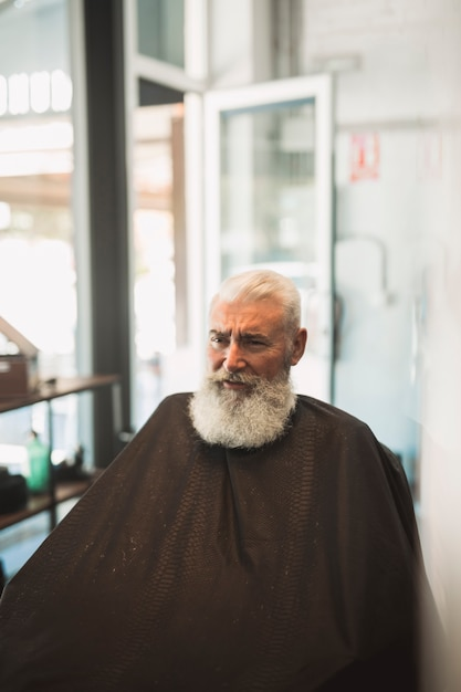 Cliente masculino sênior com capa na barbearia Foto gratuita