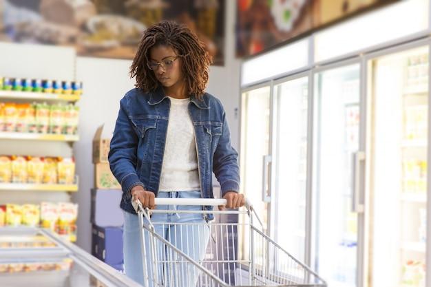 Cliente novo sério que escolhe bens no congelador Foto gratuita
