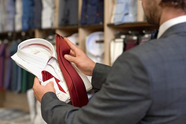 Cliente que escolhe roupas festivas para ocasiões especiais. Foto Premium