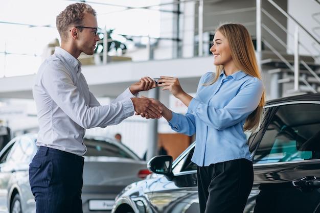 Cliente que faz uma compra em um showroom de carros Foto gratuita