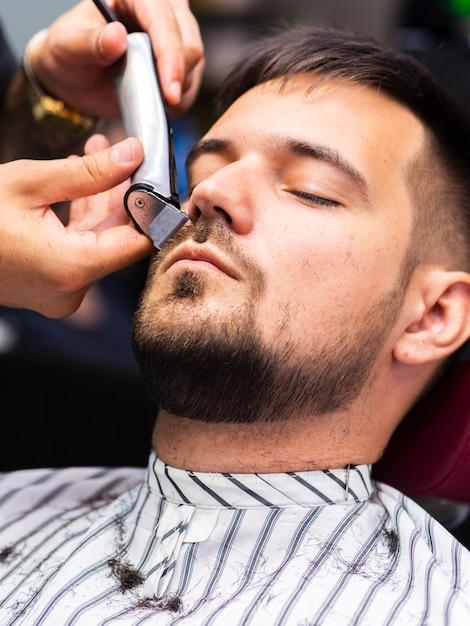 Cliente recebendo sua barba aparada Foto gratuita