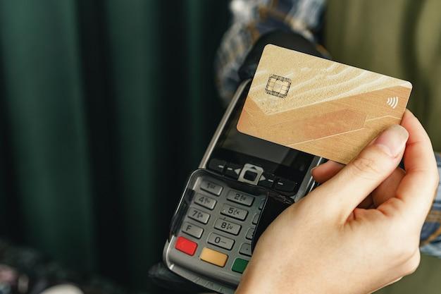 Cliente usando cartão de crédito para pagamento em café ou loja por terminal com tecnologia sem dinheiro nfc Foto Premium