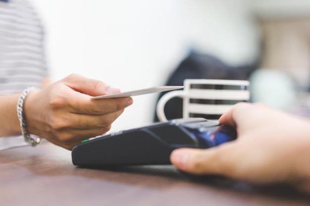 Cliente usando cartão de crédito para pagar conta usando o conceito de pagamento sem contato Foto Premium