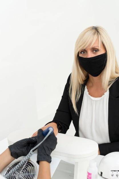 Cliente usando máscara em salão de beleza Foto gratuita