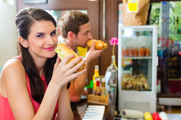 Clientes comendo hotdog na lanchonete fast food Foto Premium