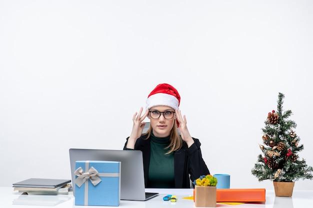 Clima de ano novo com uma mulher determinada com um chapéu de papai noel sentado a uma mesa com uma árvore de natal e um presente nela. Foto gratuita
