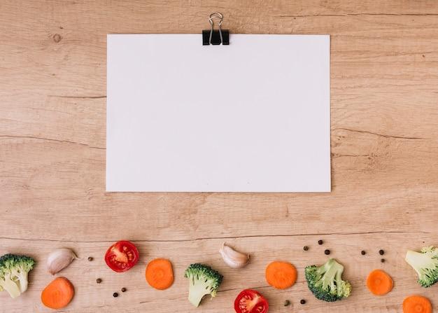 Clipe de buldogue em branco sobre papel branco sobre as fatias de cenoura; tomates cortados ao meio; brócolis; dente de alho e pimenta preta na mesa de madeira Foto gratuita