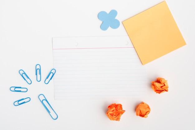 Clipe de papel azul e papel amassado com papel vazio contra fundo branco Foto gratuita