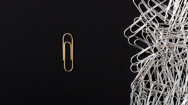 Clipe de papel dourado brilhante, destacando-se de clipes de prata sobre fundo preto Foto gratuita