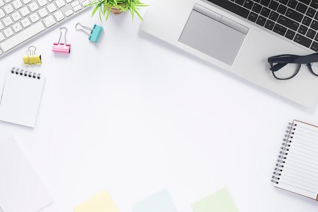 Clipes de papel; teclado; computador portátil; bloco de notas em espiral e notas auto-adesivas na mesa branca com espaço para escrever texto Foto gratuita