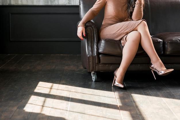 Clos-up, de, um, mulher jovem, com, cruzado, pernas, e, desgastar, dourado, calcanhares altos, sentar sofá Foto gratuita