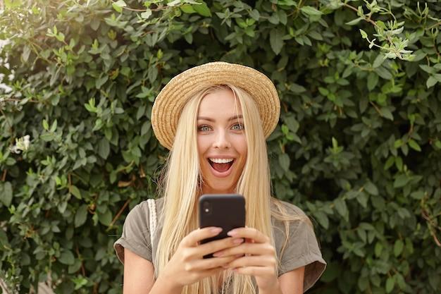 Close ao ar livre de feliz jovem loira com chapéu de palha, segurando o smartphone nas mãos e olhando com alegria, posando sobre um jardim verde em dia ensolarado Foto gratuita