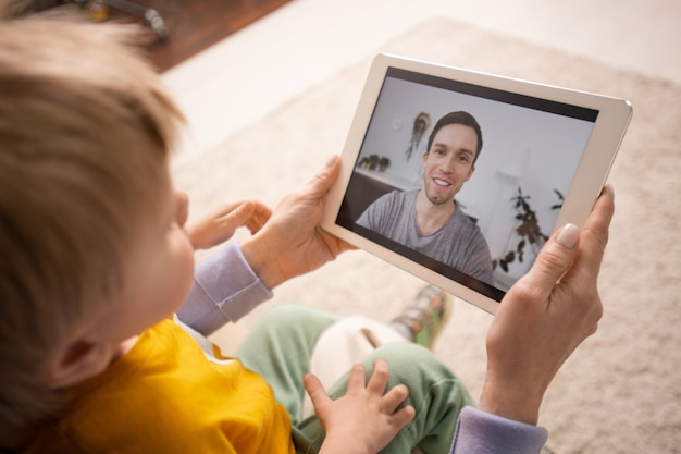Close da mãe segurando o tablet e mostrando o filho enquanto conecta o pai via aplicativo de videoconferência Foto Premium