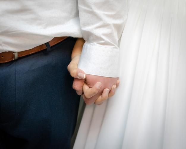 Close da noiva e do noivo segurando as mãos um do outro Foto gratuita
