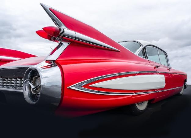 Close da parte traseira de um carro vermelho sob um céu cheio de nuvens Foto gratuita