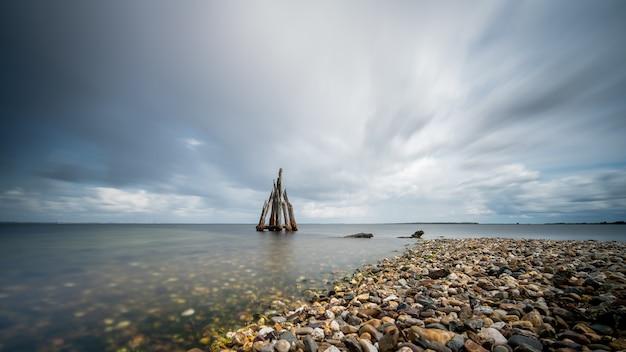Close de alto ângulo de pedras à beira-mar levando ao mar calmo Foto gratuita