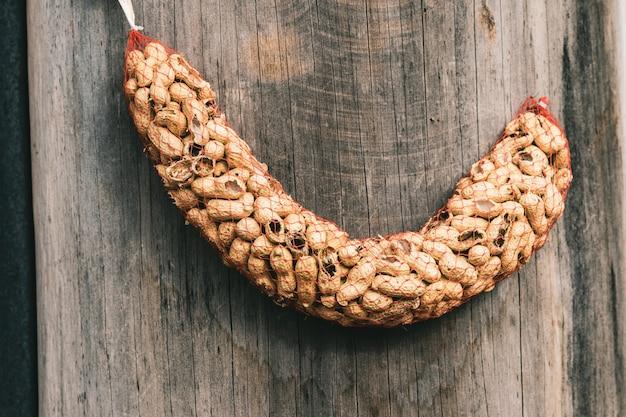 Close de amendoim em uma rede vermelha pendurada na madeira sob as luzes Foto gratuita