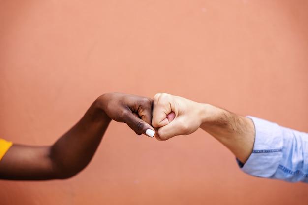 Close de amigos multiculturais dando um soco no outro. Foto Premium