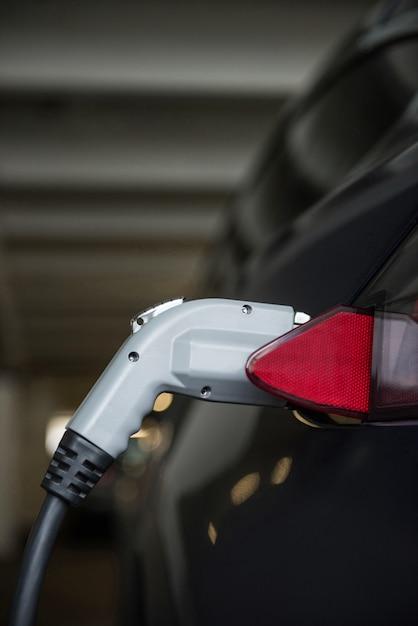 Close de carro sendo carregado com carregador elétrico Foto gratuita