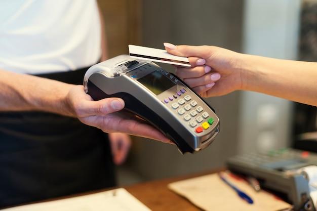 Close de cliente pagando com cartão de crédito Foto gratuita