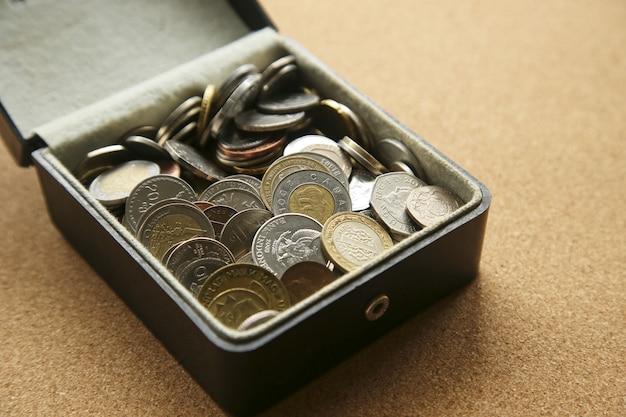 Close de diferentes moedas em uma caixa sobre a mesa Foto gratuita