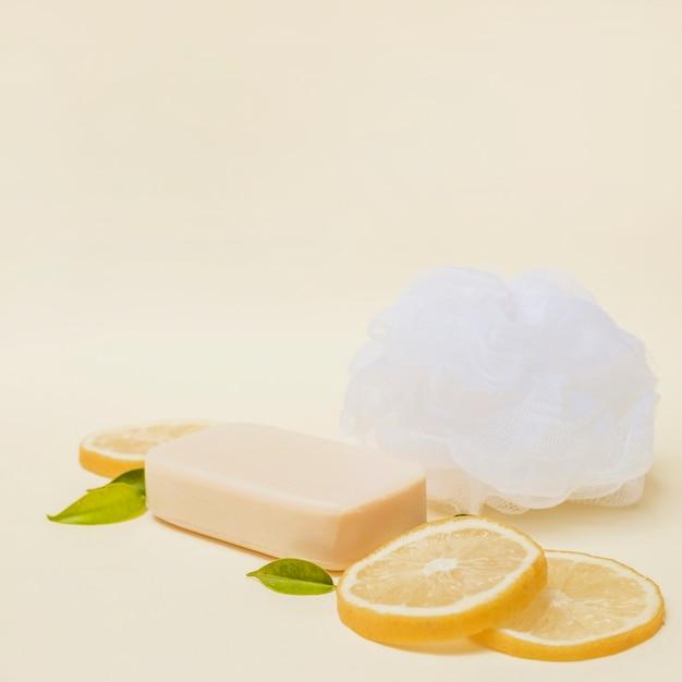 Close de fatias de limão; sabão e bucha em pano de fundo colorido Foto gratuita